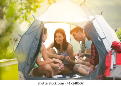 Two young couple having fun on camping trip, sitting in tent talking and playing cards