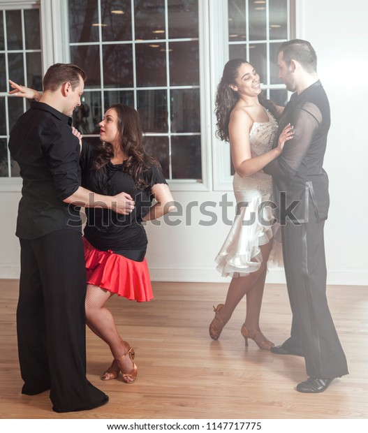 two young couples of ball dancers dancing in studio party