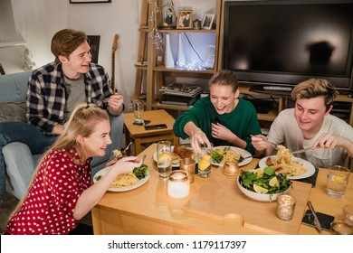 Two young couples are enjoying a dinner party at home. They are eating homemade spaghetti carbonara with garlic bread and salad.