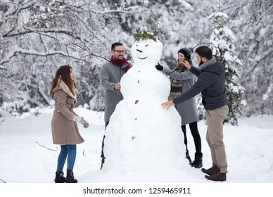 Two young couples having fun by building big snowman in park during winter holidays