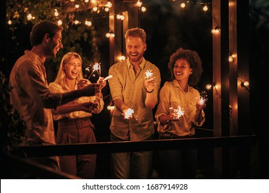 Two young couples having fun with sparklers together outside at night