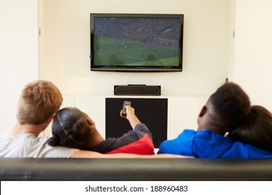Two Young Couples Watching Television At Home Together