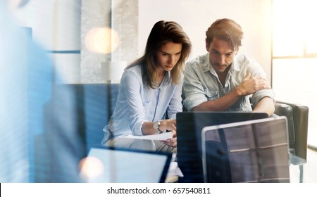 Two young coworkers working on laptop computer at sunny office.Woman holding paper documents and pointing on notebook screen. Horizontal.Blurred background.Flare