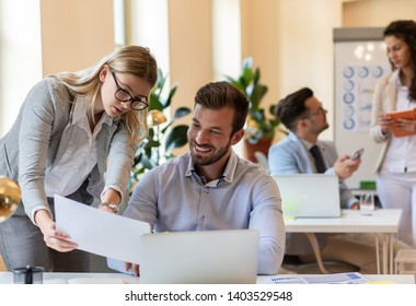 Two young coworkers working together while sitting at the office desk.