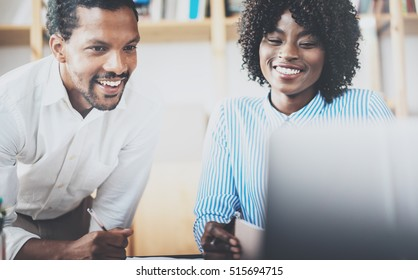 Two young coworkers working together in a modern coworking studio.African black business partners using laptop and discussing new startup project.Horizontal,blurred