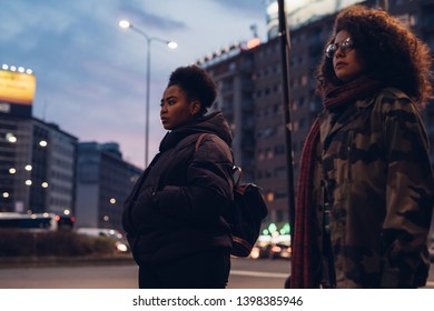 two young curly girls posing in the street and looking ahead - metropolitan, observing; find out