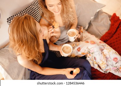 Two young curly-haired girls in pajamas drink hot cocoa, laugh. Concept of Breakfast bed, lifestyle sisterhood. Top view