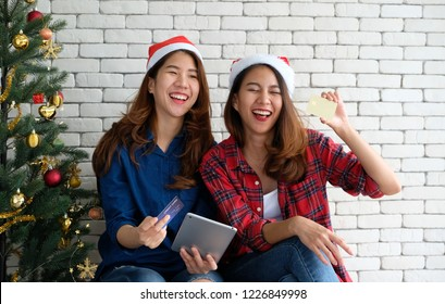 Two young cute asia women holding tablet and credit card while shopping online with happiness, Christmas holiday shopping concept