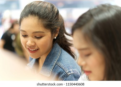 Two young cute Asian girls are looking products of cosmetic with smile face in cosmetic shop in South Korea. Friend relationship concept.