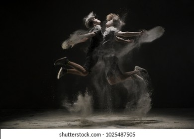 Two young dancers jumping in cloud of dust view