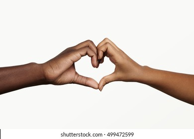 Two young dark-skinned people holding hands in shape of heart, symbolizing love, peace and unity. African man and woman showing heart-shaped hand gesture, expressing affection and togetherness