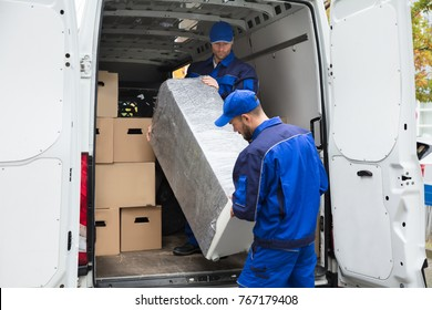 Two Young Delivery Men In Uniform Unloading Furniture From Vehicle