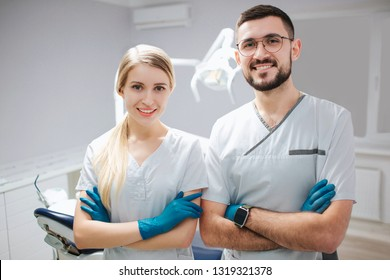 Two young dentist professionals in dentistry room. They pose on camer and smile. People hold hands crossed.