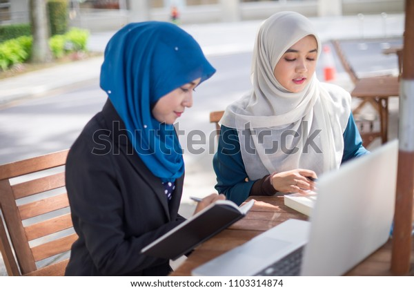 Two young and dynamic Muslim businesswoman are having a business strategy meeting to discuss their business.