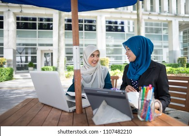 Two young and dynamic Muslim businesswomen are having a business strategy meeting to discuss their business.