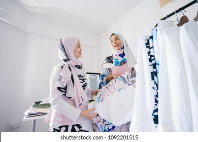 Two young and dynamic Muslim women are having a business strategy meeting to discuss their business. They sell Muslim fashion online and in-store in retail.