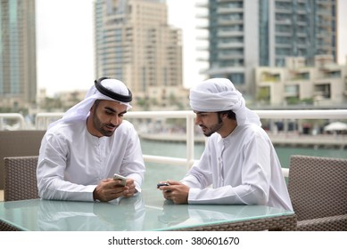 Two young Emirati arab friends talking in a restaurant