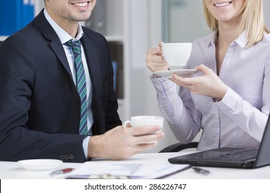 Two young employees drinking coffee at work