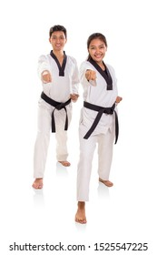 Two young energetic martial art practitioners showing their punching moves towards camera, full length shot on white background