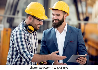 Two young engineers in construction helmets with a tablet.Construction plan, architect,designer,successful people.