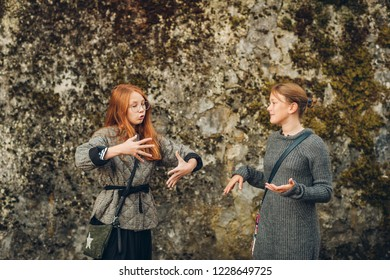 Two young expressive girls having active conversation