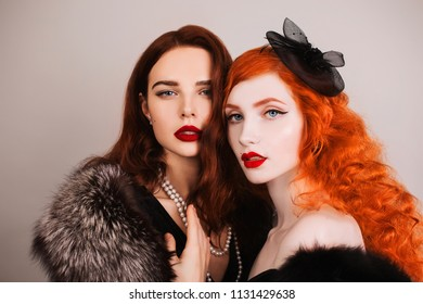 Two young fabulous lesbian girls with curly long hair in black dress on dark background. A beautiful retro woman with pale skin and red lips. Lesbian couple in a studio. Fabulous vintage models