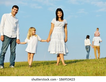 Two young families with kids walking on beautiful summer meadow enjoying and having fun