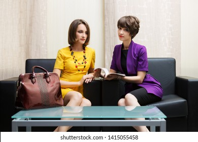 Two young fashion business women sitting on couch in showroom. Stylish female models in yellow dress and purple blazer reading a magazine