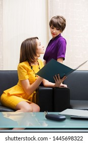Two young fashion business women siiting on couch at office Stylish female models in yellow dress and purple blazer reading a file folder
