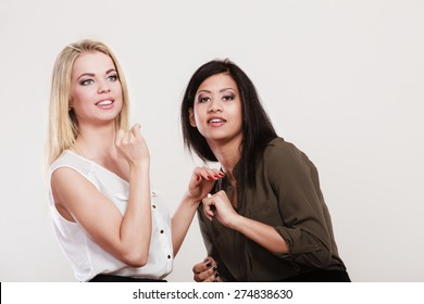 Two young fashion women caucasian and african studio portrait