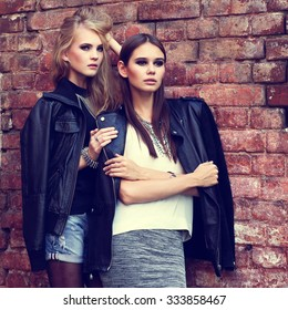 Two young fashion women outdoor. Black leather jackets, grunge style, posing near the brick wall
