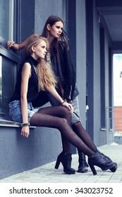 Two young fashion women posing outdoor.