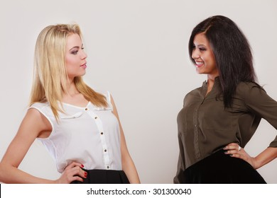 Two young fashionable women caucasian and african posing studio portrait on gray