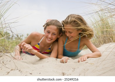 Two young female children playing in the sand at the beach
