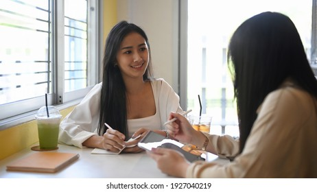 Two young female designer talking about new project while sitting together in cafe.