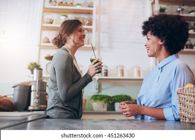 Two young female employees standing behind juice counter and talking. Juice bar owner talking with female employee.