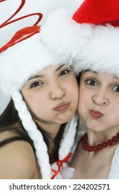 Two young female friends dressed in Christmas costumes, puffing out cheeks, looking at camera, portrait