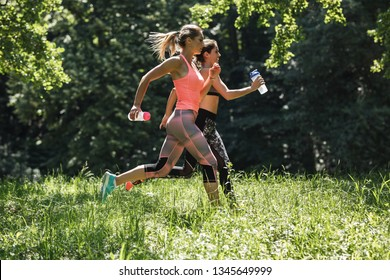 Two young female friends jogging in the nature.Spring time activity.