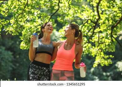 Two young female friends jogging at the woods.Embrace each other and laughing.Spring time.