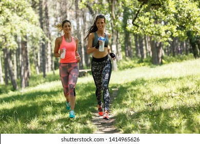 Two young female friends jogging in the nature.Summer time activity.