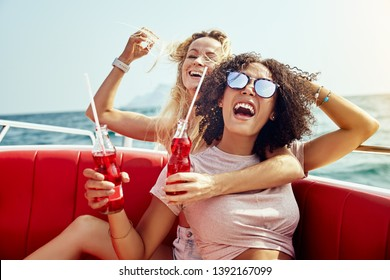 Two young female friends laughing and having drinks together while sitting on a boat on the open ocean during summer vacation