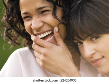 Two young female friends, one laughing