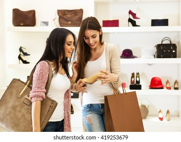 Two young female friends in a shopping,Trying shoes and making fun.