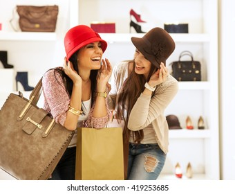 Two young female friends in a shopping,Trying hats and making fun.
