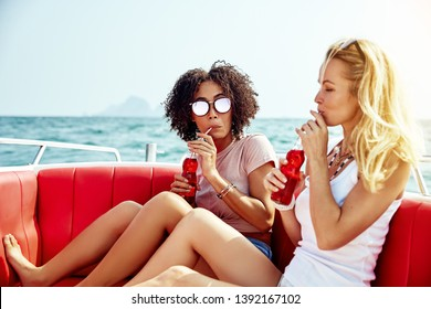 Two young female friends sipping on drinks while relaxing together on a boat on the open ocean during their summer vacation