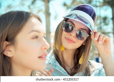 Two young female friends smile outdoors