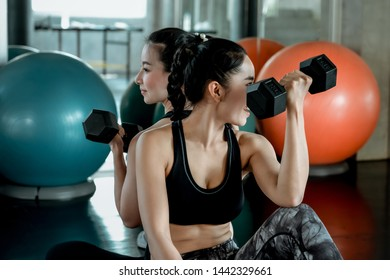 Two young female friends in sportswear work out together with dumbbells weights on the floor of a gym