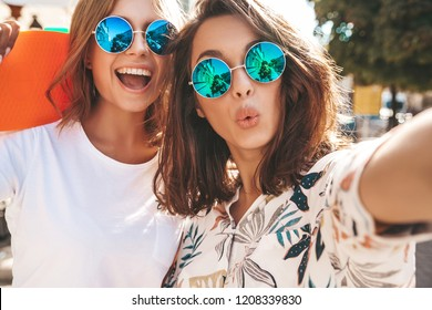 Two young female  hippie brunette and blond women. Models in hipster clothes taking selfie photos for social media on smartphone on the street background. With colorful penny skateboards
