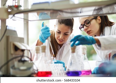 Two young female scientist doing experiments in lab.