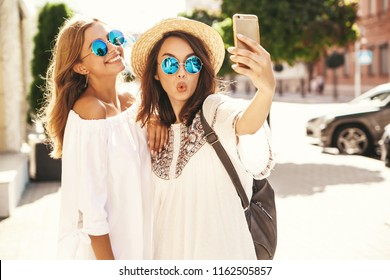 Two young female smiling hippie brunette and blond women models in summer white hipster dress taking selfie photos for social media on smartphone on the street background. Surprise face, emotions,